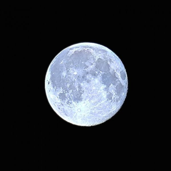 A light blue-colored full moon against a black sky.