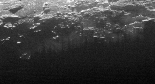 Near-Surface Haze or Fog on Pluto: In this small section of the larger crescent image of Pluto, taken by NASA's New Horizons just 15 minutes after the spacecraft's closest approach on July 14, 2015, the setting sun illuminates a fog or near-surface haze, which is cut by the parallel shadows of many local hills and small mountains. The image was taken from a distance of 11,000 miles (18,000 kilometers), and the width of the image is 115 miles (185 kilometers).View larger. |  Image credit: NASA/JHUAPL/SwRI