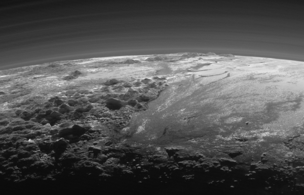 Closer Look: Majestic Mountains and Frozen Plains: Just 15 minutes after its closest approach to Pluto on July 14, 2015, NASA's New Horizons spacecraft looked back toward the sun and captured this near-sunset view of the rugged, icy mountains and flat ice plains extending to Pluto's horizon. The smooth expanse of the informally named Sputnik Planum (right) is flanked to the west (left) by rugged mountains up to 11,000 feet (3,500 meters) high, including the informally named Norgay Montes in the foreground and Hillary Montes on the skyline. The backlighting highlights more than a dozen layers of haze in Pluto's tenuous but distended atmosphere. The image was taken from a distance of 11,000 miles (18,000 kilometers) to Pluto; the scene is 230 miles (380 kilometers) across. View larger. |  Image credit: NASA/JHUAPL/SwRI)