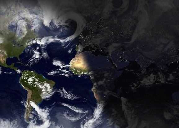 Orbital view of Earth with shadow line between lit side and dark side.