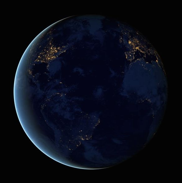 Global view of Earth at night with patches of artificial light on dark side.