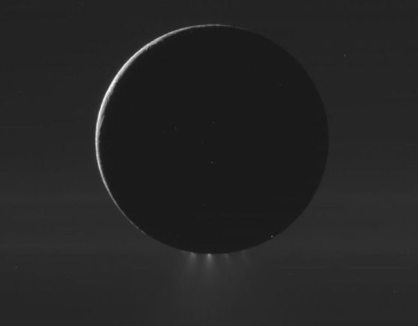 """Cassini spacecraft image from 2010 of Saturn's moon Enceladus. The moon is backlit, with its dark outline crowned by glowing jets from the south polar region. Notice that there are several separate jets, or sets of jets, emanating from the fissures known to scientists as """"tiger stripes."""" Image via NASA/JPL/SSI"""