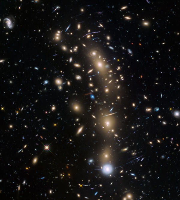 View larger. | This image from the NASA/ESA Hubble Space Telescope shows the galaxy cluster MACS J0416.1–2403. This is one of six being studied by the Hubble Frontier Fields programme, which together have produced the deepest images of gravitational lensing ever made. Due to the huge mass of the cluster it is bending the light of background objects, acting as a magnifying lens. Astronomers used this and two other clusters to find galaxies which existed only 600 to 900 million years after the Big Bang.