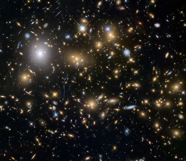 View larger. | This image from the NASA/ESA Hubble Space Telescope shows the galaxy cluster MACSJ0717.5+3745. This is one of six being studied by the Hubble Frontier Fields programme, which together have produced the deepest images of gravitational lensing ever made. Due to the huge mass of the cluster it is bending the light of background objects, acting as a magnifying lens. It is one of the most massive galaxy clusters known, and it is also the largest known gravitational lens. Of all of the galaxy clusters known and measured, MACS J0717 lenses the largest area of the sky.