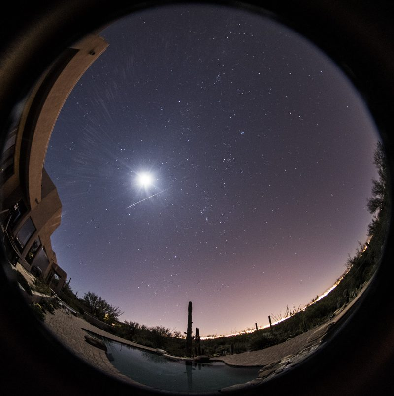 Circular panorama with stars, bright moon, and one meteor streak.