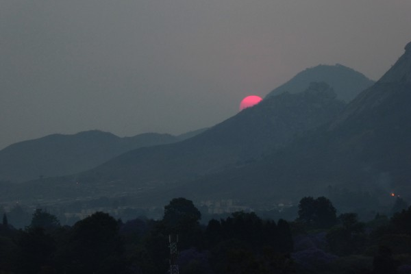 Setting sun colored magenta by smoke haze, Mutare, Zimbabwe, October 10.  Photo by Peter Lowenstein.