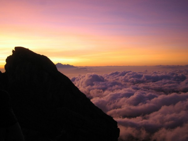 Sunset from the 3,148 m high summit of Gunung Agung. The peak in the distance is G. Abang, a remnant of a far loftier peak, Ancestral Batur. Image credit: WikimediaCommons photo by Mrllmrll