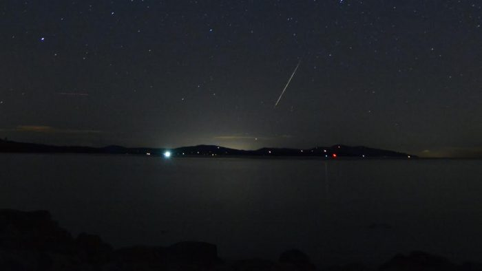 Meteor streak over low-lying hills with sea in foreground.