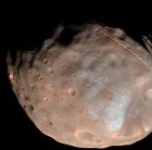 New modeling indicates that the grooves on Mars' moon Phobos could be produced by tidal forces – the mutual gravitational pull of the planet and the moon. Initially, scientists had thought the grooves were created by the massive impact that made Stickney crater (lower right). Image via NASA/JPL-Caltech/University of Arizona