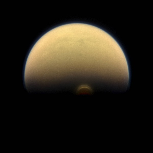 "As winter sets in at Titan's south pole, a cloud system called the south polar vortex (small, bright ""button"") has been forming, as seen in this 2013 image. Image credit: NASA/JPL-Caltech/Space Science Institute"