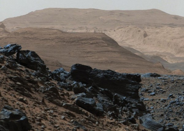 Dark rocks on route to Mountains. Diverse terrain is visible on this image taken on Mount Sharp on April 10, 2015. The color has been approximately white-balanced to resemble how the scene would appear under daytime lighting conditions on Earth. Image via NASA/JPL-Caltech/MSSS