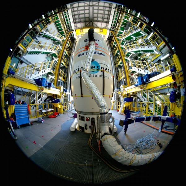 LISA Pathfinder, ready for launch.  In this image, taken with an ultra-wide angle fisheye lens on 19 November, the spacecraft is hidden from view, encapsulated in the 'upper composite' of its Vega rocket. Only the aerodynamic fairing at the top of the fully assembled launcher is visible, while the lower stages are hidden by the movable access platform. The hose is part of the air conditioning system that regulates the environment inside the fairing. Image via ESA.
