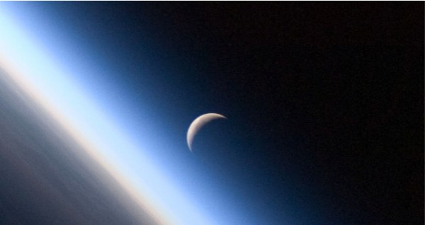 Orbital view of Earth's straight horizon vertically on left with crescent moon standing out to its right.