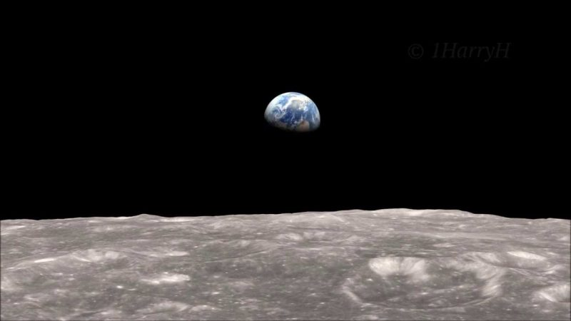 Half Earth floating in black sky over gray, cratered surface of the moon.