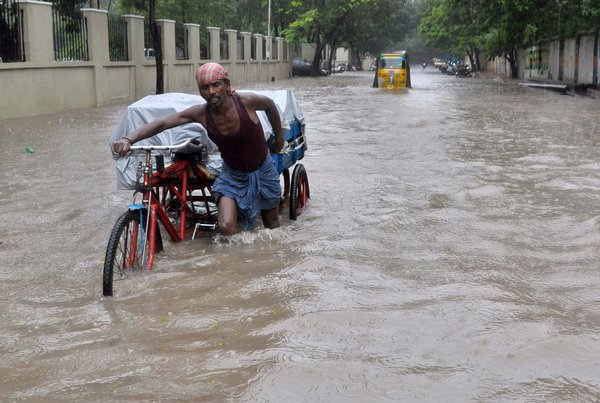An Indian labourer pushes his cycle trishaw through floodwaters in Chennai on December 1, 2015, during a downpour of heavy rain in the southern Indian city.  Heavy rains pounded several parts of the southern Indian state of Tamil Nadu and inundating most areas of Chennai, severely disrupting flights, train and bus services and forcing the postponment of half-yearly school exams.   AFP PHOTO/STR / AFP / STRDEL        (Photo credit should read STRDEL/AFP/Getty Images)