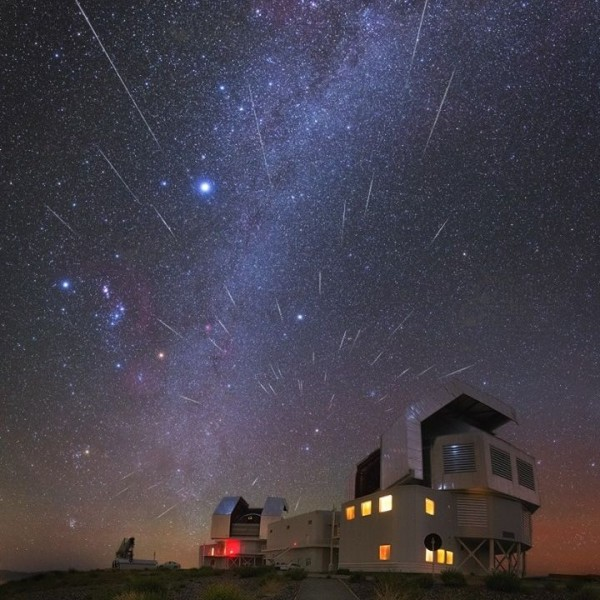 Many thin streaks of light in sky over observatory buildings, with Orion visible.
