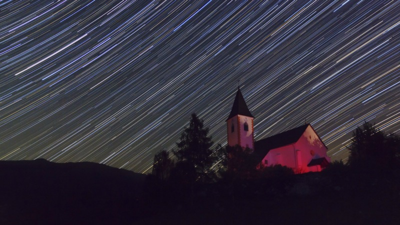 Very many long parallel bright streaks in the night sky over a small old church.