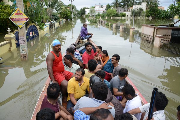 Indian rescue workers on a boat move people to safety amidst water-logged houses in a flooded suburb of Chennai on November 17, 2015.   India has deployed the army and air force to rescue flood-hit residents in the southern state of Tamil Nadu, where at least 71 people have died in around a week of torrential rains.  AFP PHOTO        (Photo credit should read STR/AFP/Getty Images)