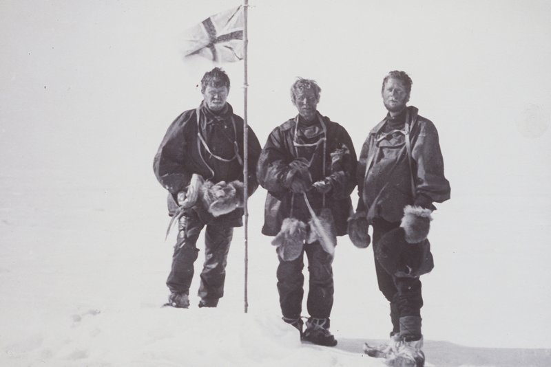 three men next to a flagpole