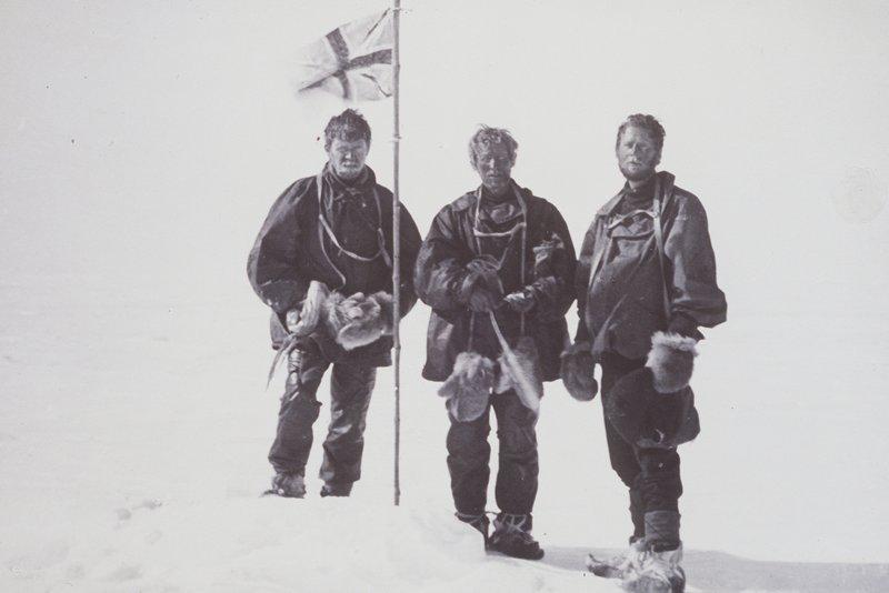 three men next to a flagpole