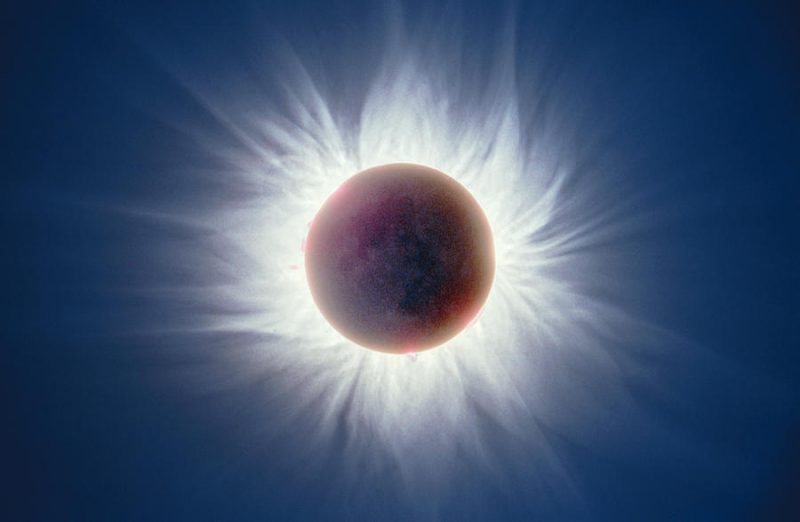 picture of eclipse, dark circle with white light flaring out around it.