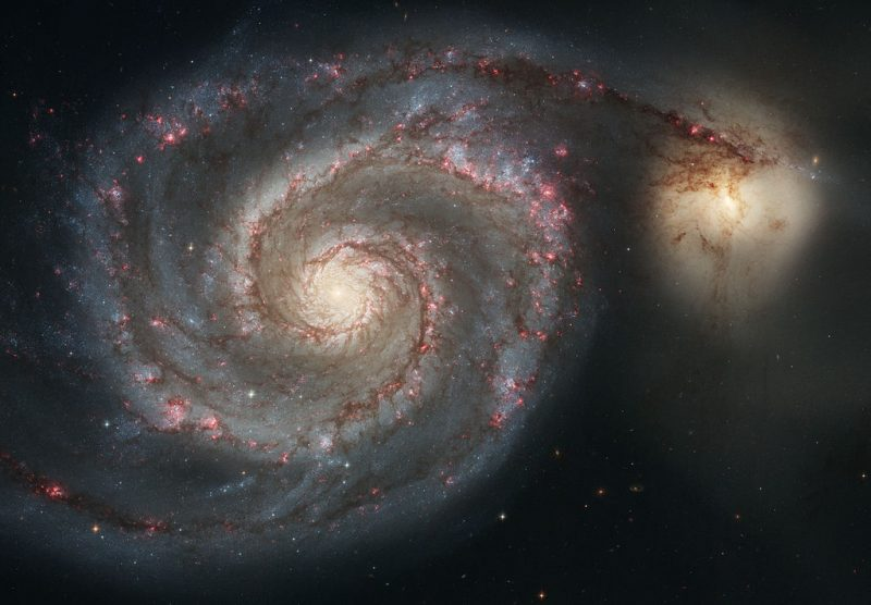flat-on view of spiral galaxy with smaller one attached like a tail
