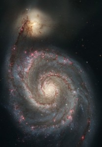 Galaxy with yellow-white center, two spiral arms dotted with pink areas. Bright yellow patch at end of one arm.