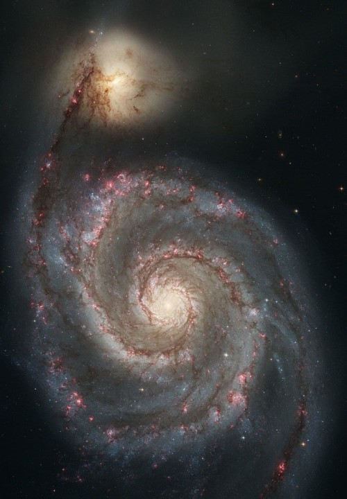 Yellow-white center, two spiral arms dotted with pink areas. Bright yellow patch at end of one arm.