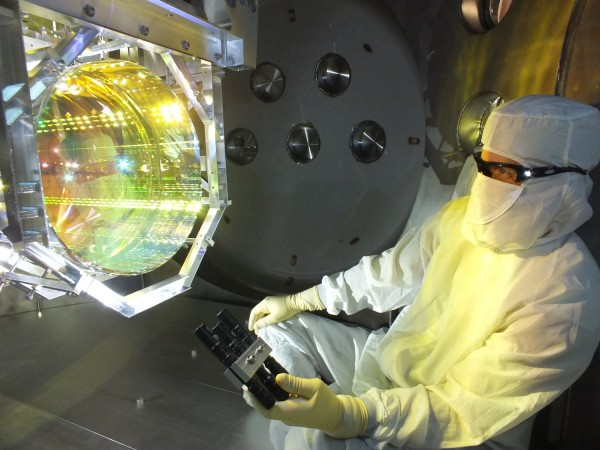 A LIGO optics technician inspects one of LIGO's core optics (mirrors) by illuminating its surface with light. Image via  Matt Heintze/Caltech/MIT/LIGO Lab.