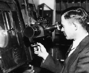 Clyde Tombaugh looking into eyepiece of a device to 'blink plates' at Lowell Observatory.