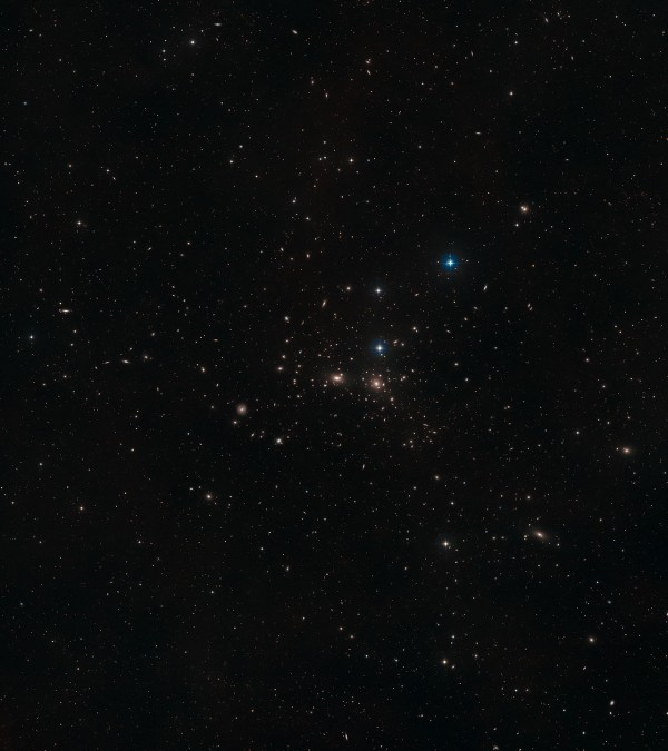 This image shows a ground-based wide-field view of the region around NGC 4889 from the Digitized Sky Survey 2. Image credit: NASA, ESA, Digitized Sky Survey 2