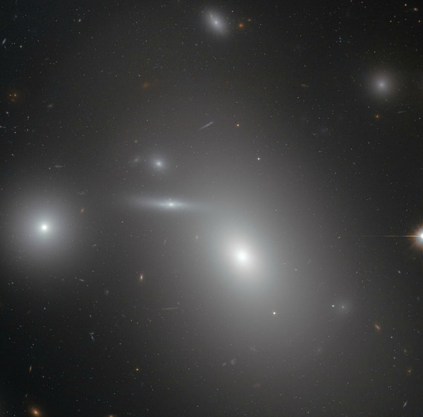 This image shows the elliptical galaxy NGC 4889 in front of hundreds of background galaxies, and deeply embedded within the Coma galaxy cluster. Well-hidden from human eyes, there is a gigantic supermassive black hole at the centre of the galaxy. Image credit: NASA & ESA
