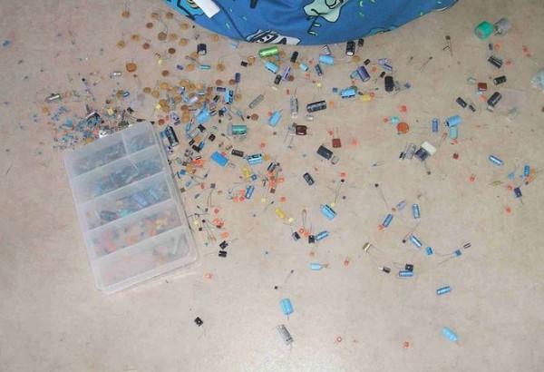 Diodi sparsi e altri piccoli componenti elettronici fuoriusciti da una scatola di plastica.