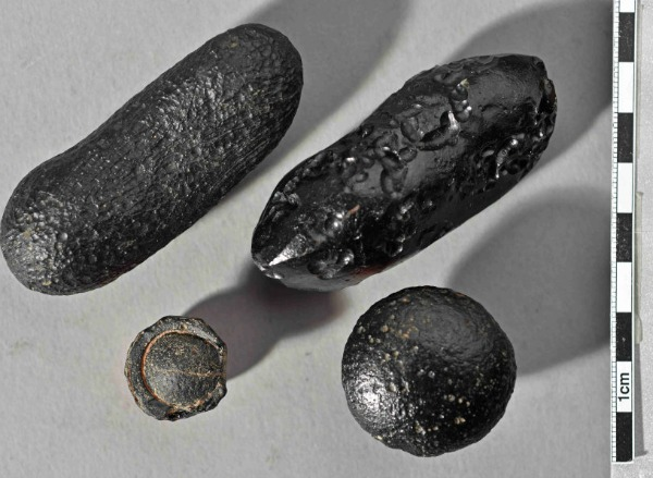 Tektites of different shapes from Australia. The force of the impact hurled the glass bodies thousands of kilometres. Some left the earth's atmosphere and acquired their flanged edge on re-entry into the atmosphere (bottom left). Image credit: © Institute of Earth Sciences, Heidelberg University