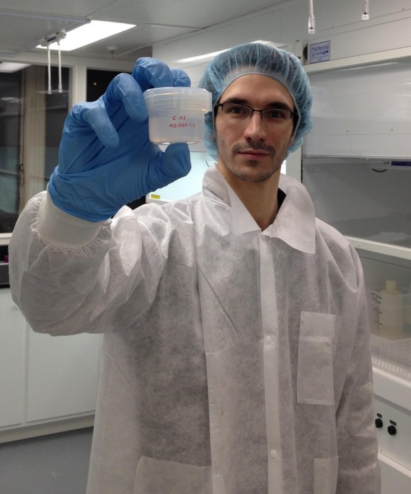 Francois Tissot, in the clean lab, holding a beaker containing a refractory inclusion dissolved in strong acids. Image credit: Francois L.H. Tissot.