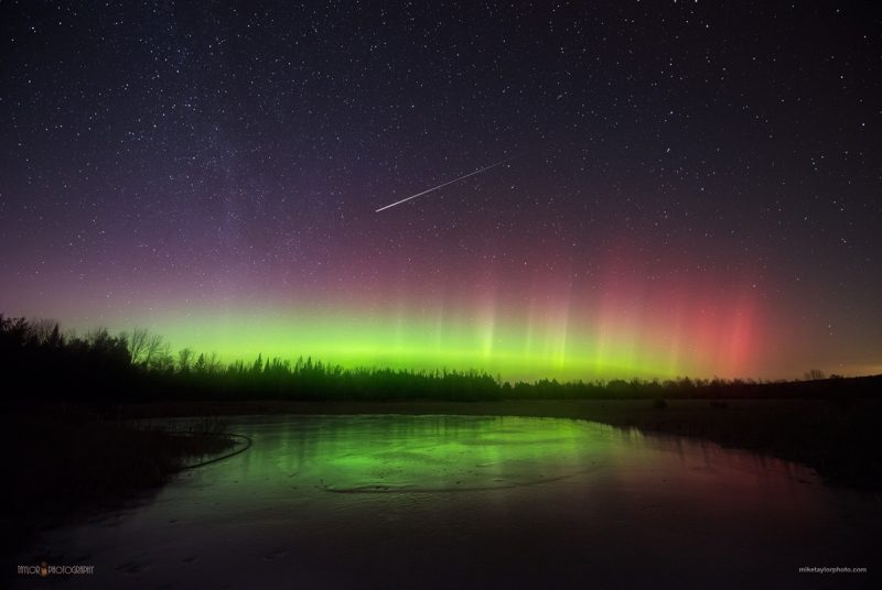 The green glow of northern lights on the horizon with a bright meteor streaking above.