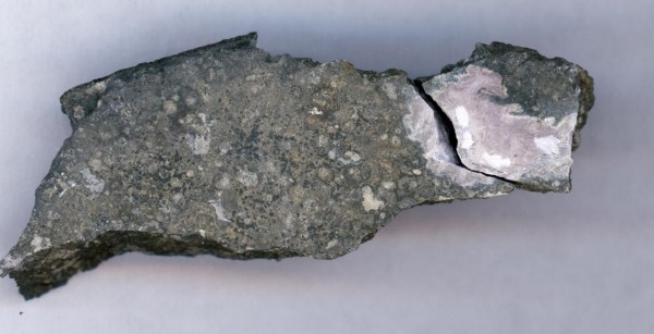 A close-up photo of a meteorite sample, 0.59 inches (1.5 centimeters) across showing a ceramic-like refractory inclusion (in pink) embedded in the meteorite. Refractory inclusions are the oldest-known rocks in the solar system (4.5 billion years old). The analysis of the uranium isotope ratios of such inclusions showed that a long-lived curium isotope was present early in the solar system when this inclusion was formed. Image credit: Origins Lab, University of Chicago.