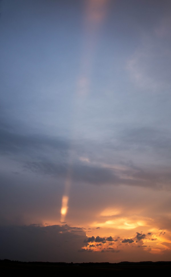 Pillar of light coming up from dark clouds against a yellow sunset.