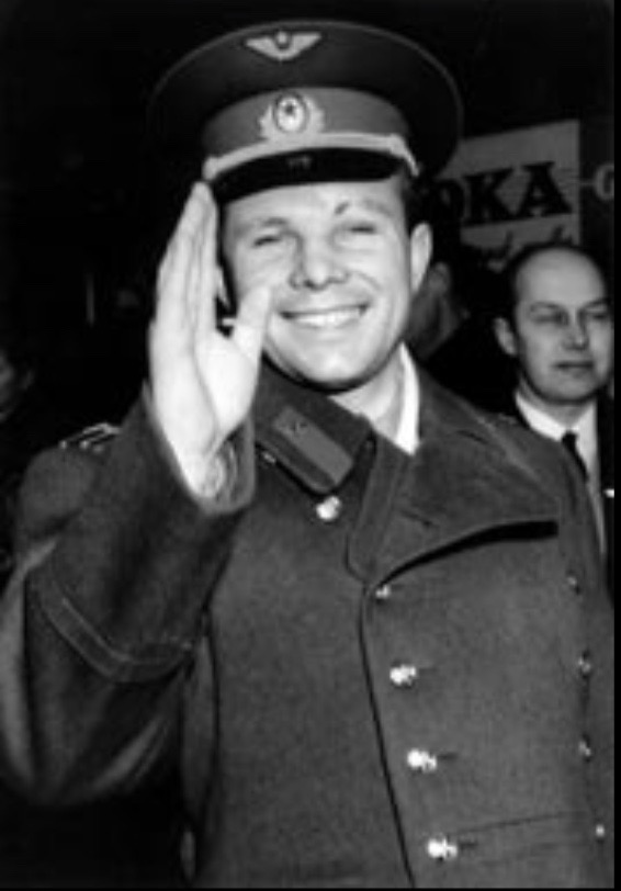 Smiling man in Soviet uniform with cap. He is waving at the camera.
