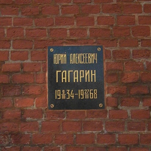 Dark metal plaque on brick wall with dates and name in gold Cyrillic characters.