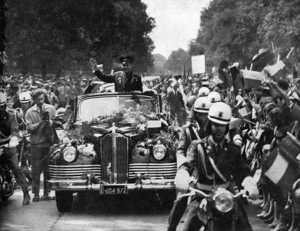 Waving man in open-top car surrounded by onlookers.