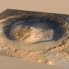 View larger. | It's called Mount Sharp, but it's really just a mound on Mars, in the center of the Gale Crater, where the Curiosity rover set down in 2013. Gale Crater, the landing spot of NASA's Curiosity Mars rover, has a three-mile-high mound at its center called Mount Sharp. The circle indicates the rover's landing place. The blue line is its path. New research shows mounds like this may have been carved by wind over billions of years. Image via NASA/JPL.