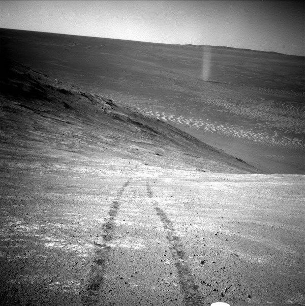 From its perch high on a ridge, NASA's Mars Exploration Rover Opportunity recorded this image of a Martian dust devil twisting through the valley below. The view looks back at the rover's tracks leading up the north-facing slope of