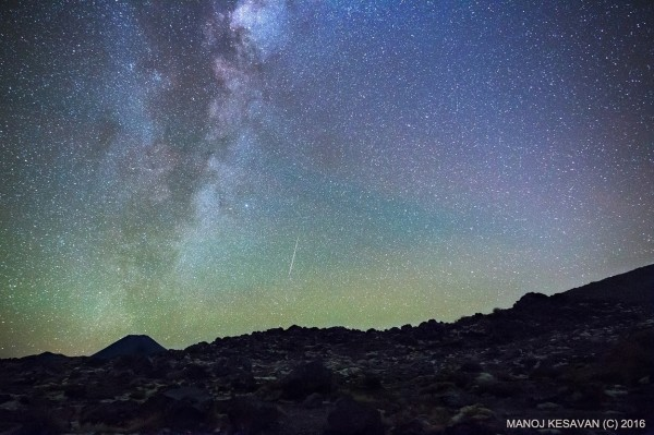 Milky Way rising in a dark geen sky with a short vertical white streak near the horizon.