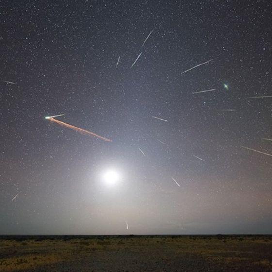 Many bright white streaks and glowing moon above desert horizon.
