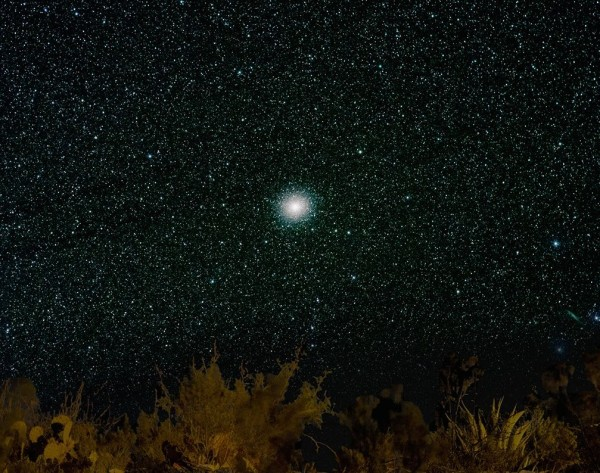 Telescopic view of fuzzy dot, stars visible around edges, in star field.