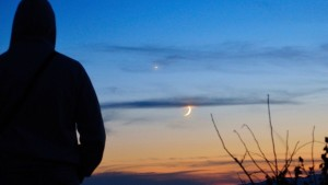 Silhouette of a man against the sunset sky with bright planet and crescent moon.