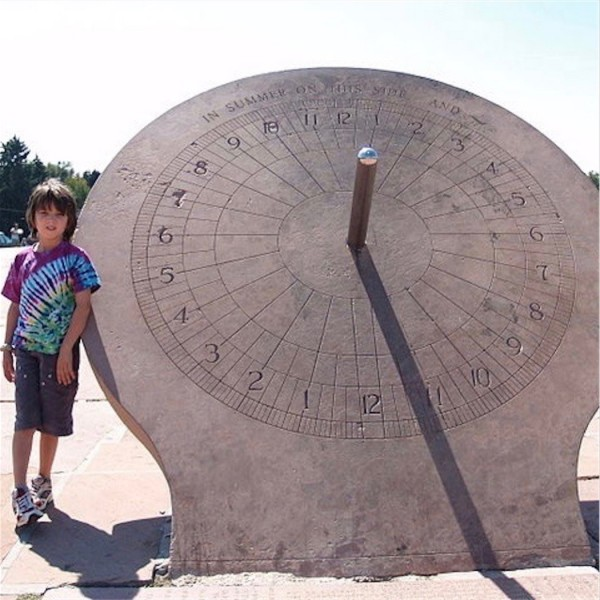 Equatorial sundial at Denver's Crammer Park, when it is a little past 11 a.m. by the sun. The shadow moves clockwise, with the afternoon hours on the left.