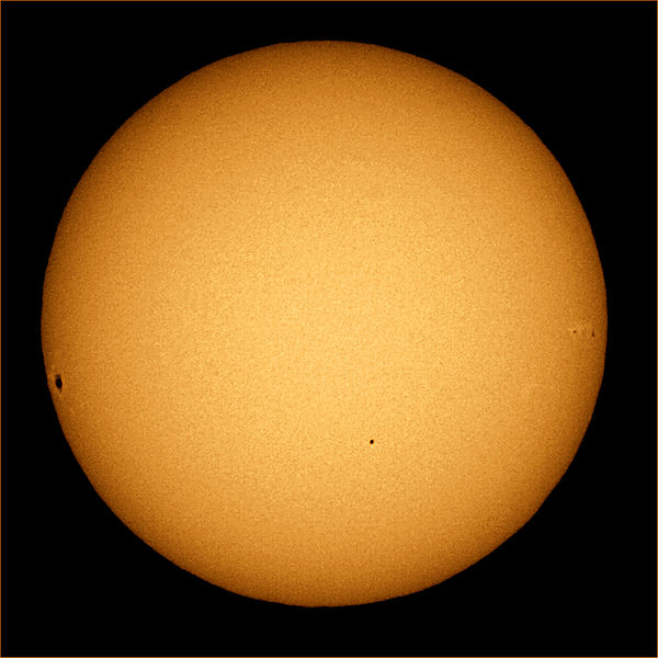 Mercury appears as a tiny black dot in front of the sun.