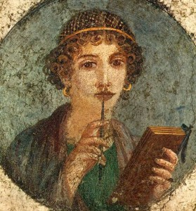 A fresco from Pompeii depicting of a Woman believed to be Sappho, holding wax tablets and stylus. Image credit: Herkulaneischer Meister via Wikimedia Commons.